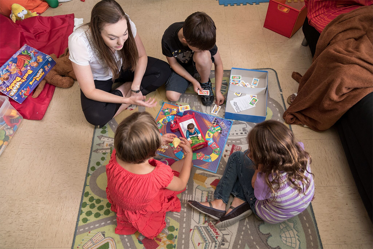 Kids playing board game with teacher on the floor