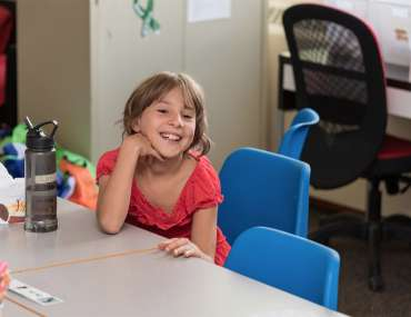 Girl smiling and sitting at the desk