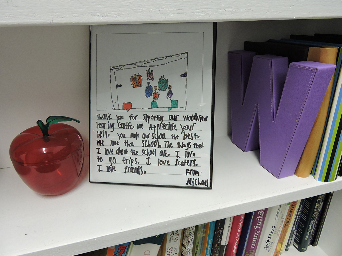 Framed letter from student on a bookshelf