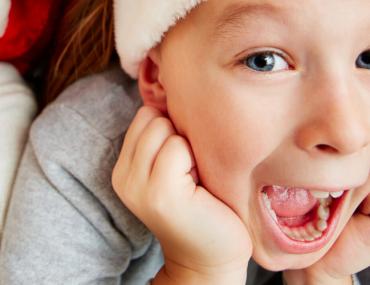 children laughing wearing santa hats